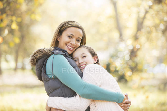 Portrait of smiling mother and daughter hugging outdoors — Stock Photo