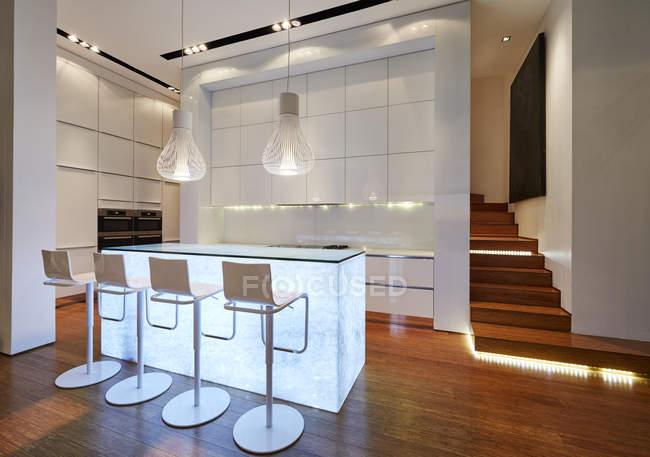 Illuminated modern luxury kitchen and staircase — Stock Photo