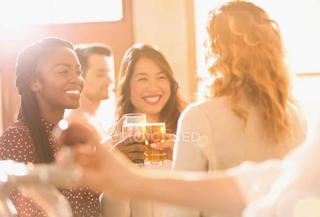 Mulheres sorridentes amigos brindar copos de cerveja no bar ensolarado — Fotografia de Stock