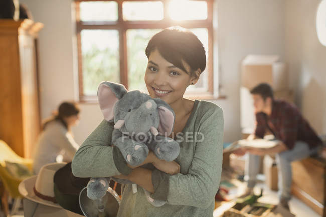Portrait smiling young woman holding stuffed elephant — Stock Photo