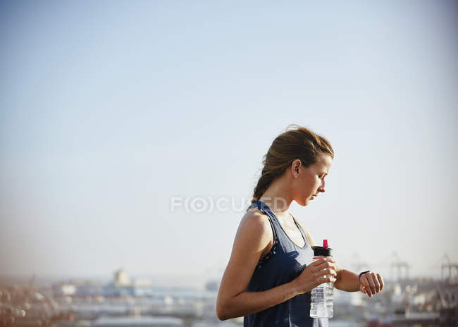 Female runner with water bottle checking smart watch fitness tracker under sunny bleu sky — Stock Photo