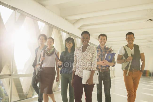 Уверенные креативные бизнесмены, идущие по солнечному коридору — стоковое фото