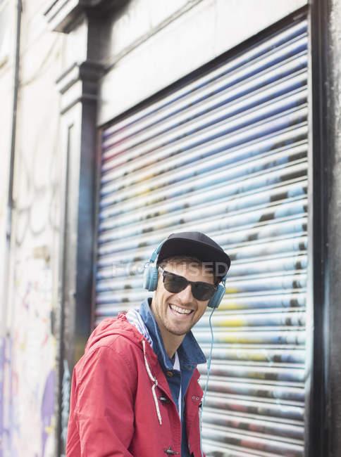 Man listening to headphones near graffiti wall — Stock Photo