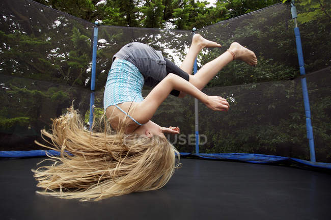 Girl jumping on trampoline outdoors — Stock Photo