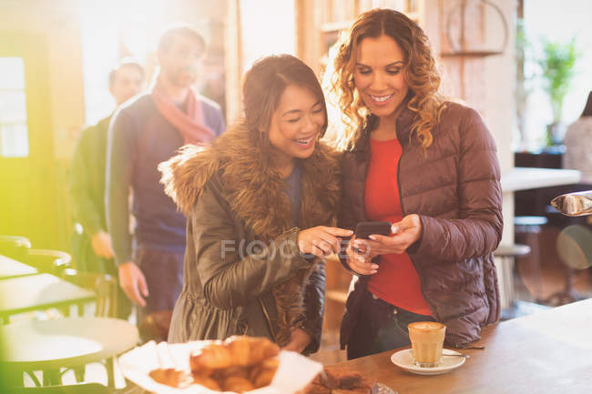 Жінки друзів за допомогою мобільного телефону в кафе — стокове фото