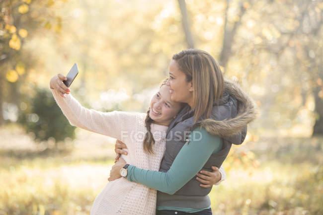 Мать и дочь принимая selfie на открытом воздухе — стоковое фото