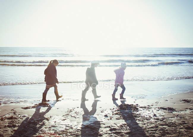 Frères et sœurs en vêtements chauds marchant dans le sable mouillé sur une plage ensoleillée — Photo de stock