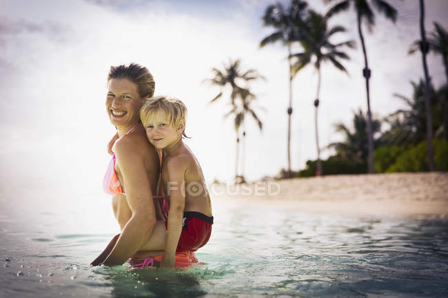 Portrait smiling mother piggybacking son in tropical ocean — Stock Photo