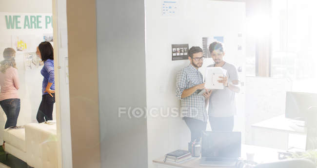 Creative businessmen reviewing paperwork in sunny office — Stock Photo