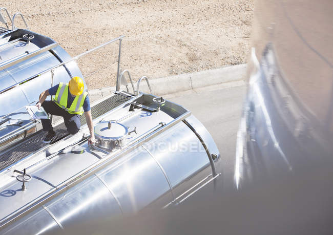 Worker on platform above stainless steel milk tanker — Stock Photo