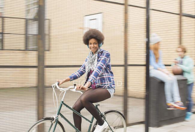Heureuse jeune femme à vélo sur la rue de la ville — Photo de stock