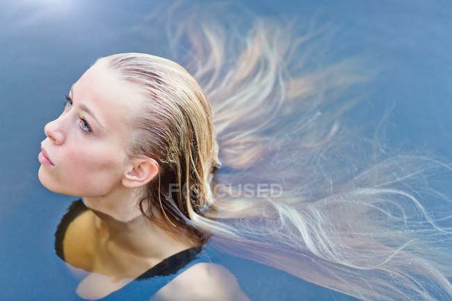 Portrait beautiful blonde teenage girl with long hair floating in swimming pool — Stock Photo