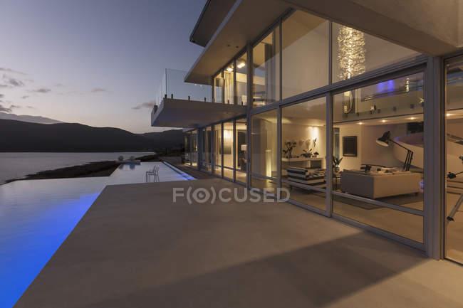 Спокойный современный роскошный дом с бассейном и видом на сумерки океана — стоковое фото
