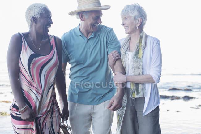 Senioren gehen am Strand spazieren — Stockfoto