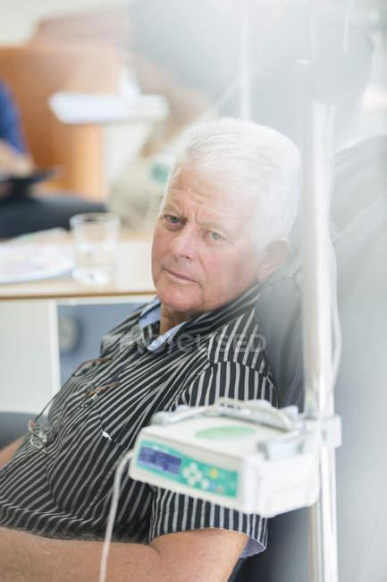 Hombre mayor que recibe perfusión intravenosa en el hospital - foto de stock