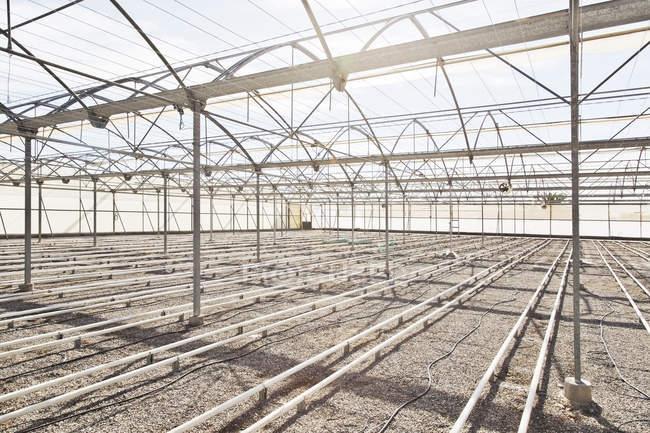Bewässerungsrohre in leerem Gewächshaus — Stockfoto