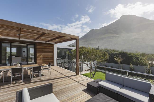 Casa ensolarada vitrine varanda exterior com vista para a montanha — Fotografia de Stock