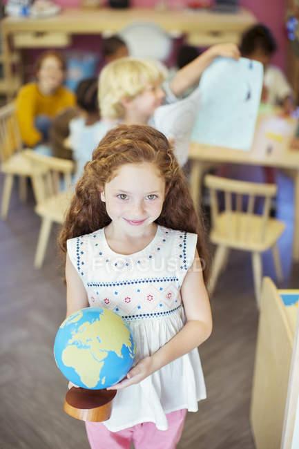 Student hält Globus im Klassenzimmer — Stockfoto