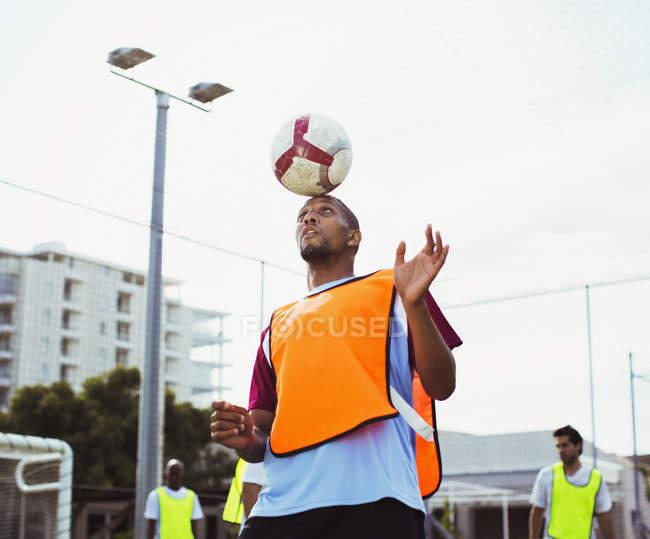Fußballer hält Ball am Kopf — Stockfoto