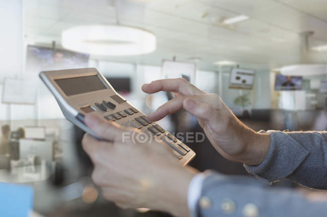 Close up businessman using large calculator in office — Stock Photo