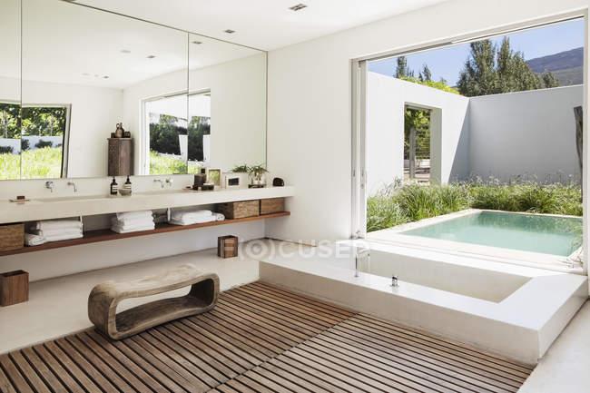 Modern bathroom overlooking luxury soaking pool — Stock Photo
