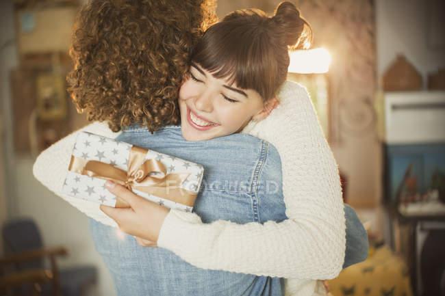 Entusiasta joven mujer abrazando novio celebración cumpleaños regalo - foto de stock