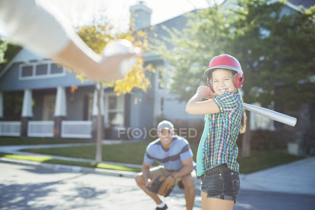 Family playing baseball in street — Stock Photo