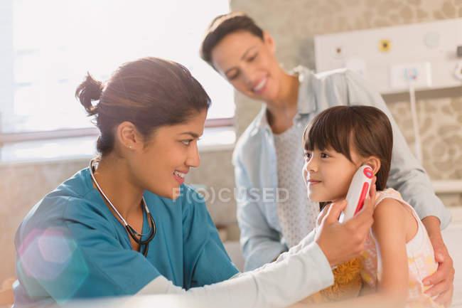 Женщины медсестра с использованием цифровой термометр ухо больная в экзаменационную комнату — стоковое фото