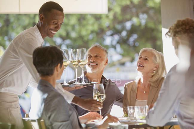 Camarero sirviendo vino blanco a parejas en mesa de restaurante - foto de stock