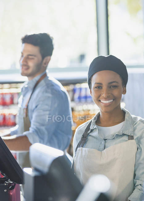 Portrait smiling young female cashier working at grocery store market checkout — Stock Photo