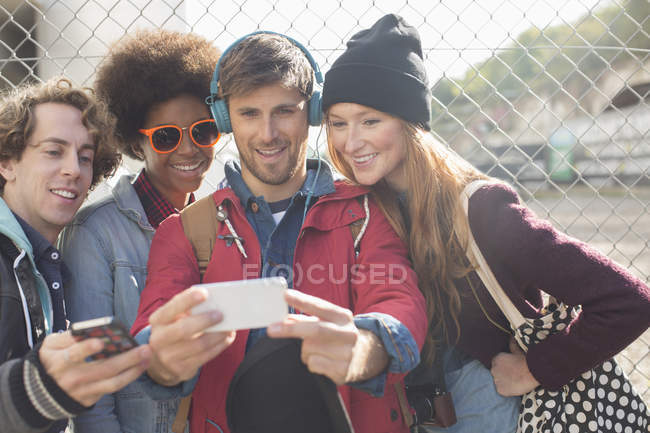 Friends taking self-portrait with camera phone outdoors — Stock Photo