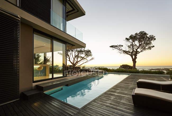 Современный роскошный витринный внутренний дворик и бассейн с видом на закат океана — стоковое фото