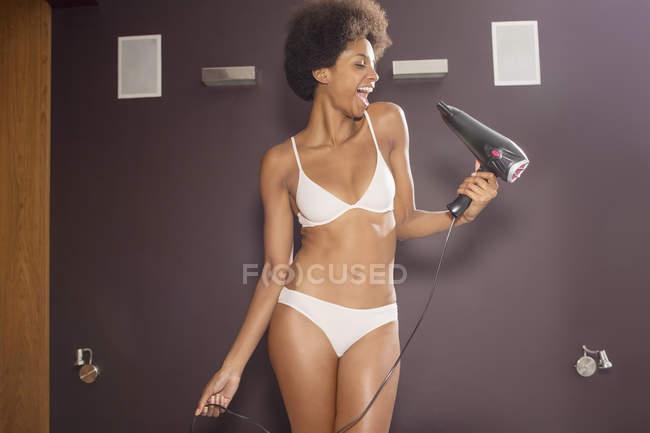 Mujer en sujetador y bragas cantando en secador de pelo en el baño - foto de stock