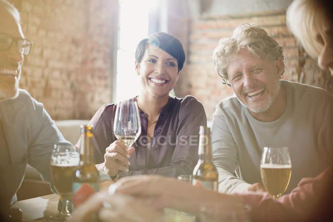 Parejas riéndose bebiendo vino blanco y cerveza en la mesa del restaurante - foto de stock