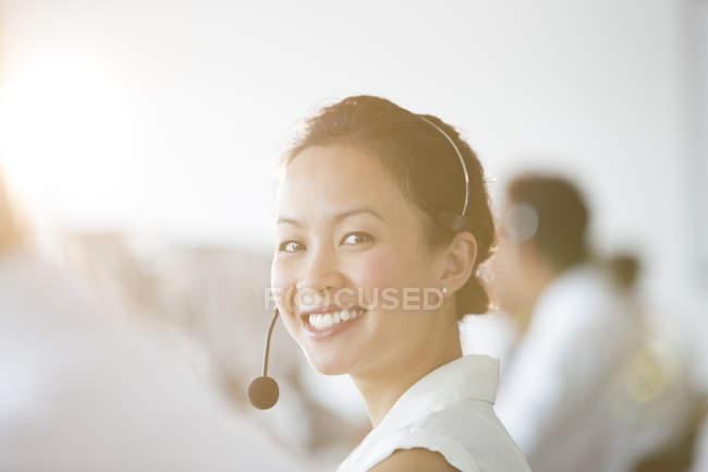 Businesswoman wearing headset in office — Stock Photo