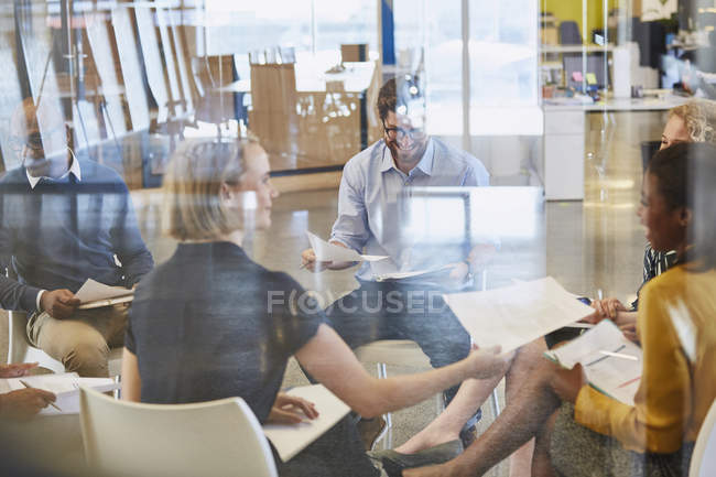 Business people reviewing paperwork in meeting at modern office — Stock Photo