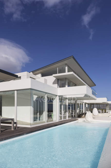 Sunny, tranquilo casa de luxo moderno vitrine exterior com piscina sob o céu azul — Fotografia de Stock