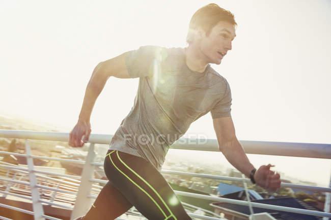 Determined male runner running on sunny footbridge — Stock Photo