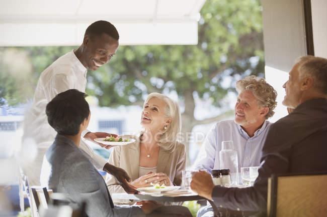 Camarero sirviendo comida a parejas en mesa de restaurante - foto de stock