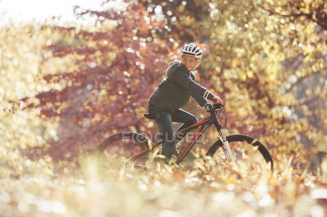 Menino andar de bicicleta na floresta com folhas de outono — Fotografia de Stock