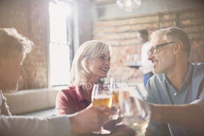 Sorrindo amigos brindando a copos de cerveja e vinho no restaurante — Fotografia de Stock