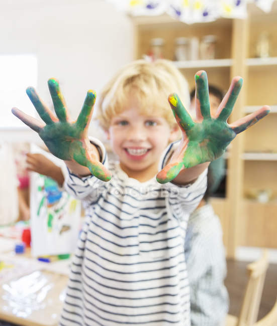 Student showing off messy hands in classroom — Stock Photo