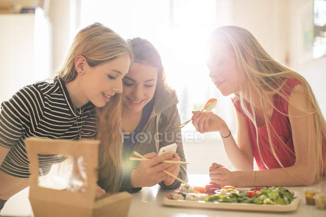 Adolescenti che mangiano sushi e texting con il telefono cellulare in cucina soleggiata — Foto stock