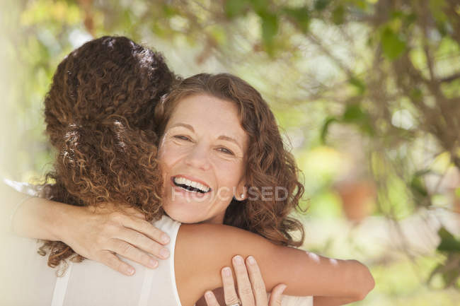 Happy beautiful mother and daughter hugging outdoors — Stock Photo
