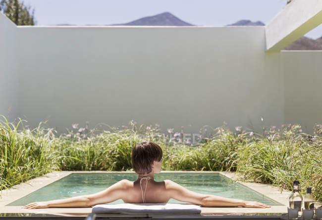 Женщина расслабляется в роскошном бассейне — стоковое фото