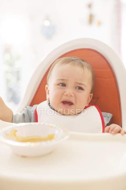 Малыша плача в высоком стуле — стоковое фото