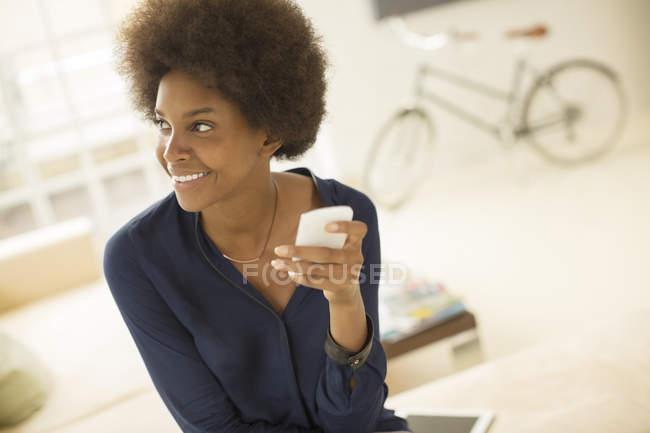 Mulher usando telefone celular na sala de estar em casa — Fotografia de Stock