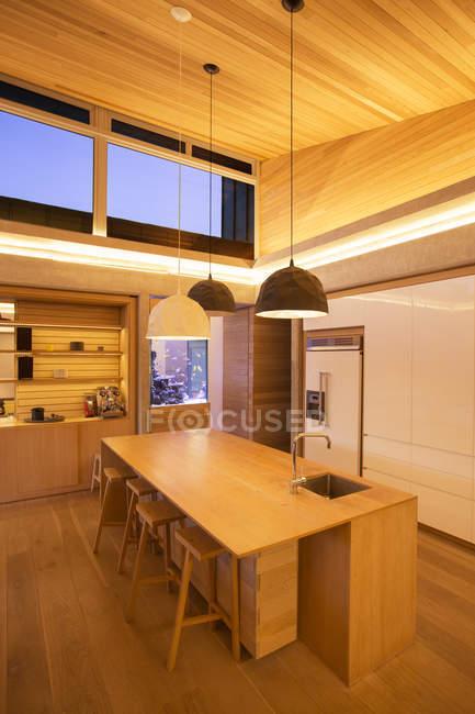 Illuminated slanted wood ceiling and pendant lights over kitchen island — Stock Photo