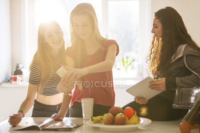 Ragazze adolescenti prendendo selfie con la fotocamera del telefono in cucina — Foto stock