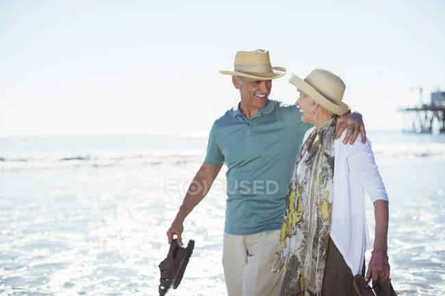 Seniorenpaar geht am Strand spazieren — Stockfoto